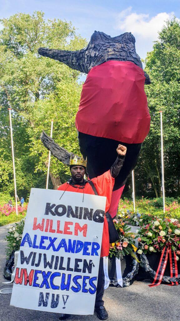 Keti Koti man met bord Koning Willem Alexander excuses nu